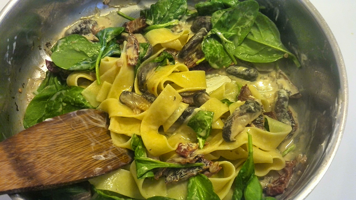 Combing ingredients and pasta - pappardelle, shiitake mushrooms, sun dried tomatoes and cream cheese