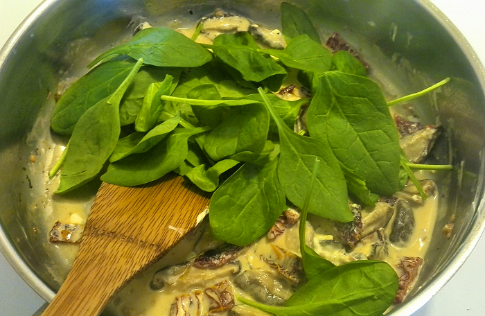 Stirring in the spinach into my easy Italian pasta recipe