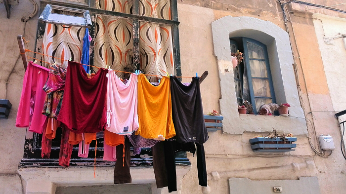 Colourful hanging laundry with a cat on the windowsill in Valletta Malta
