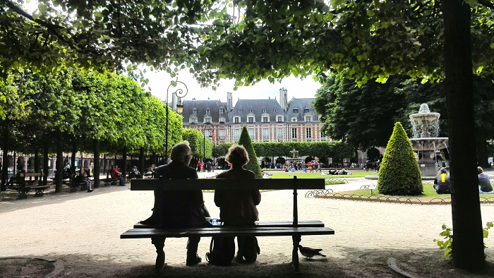 Man and woman sitting on a bench in Places des Vosges | Paris