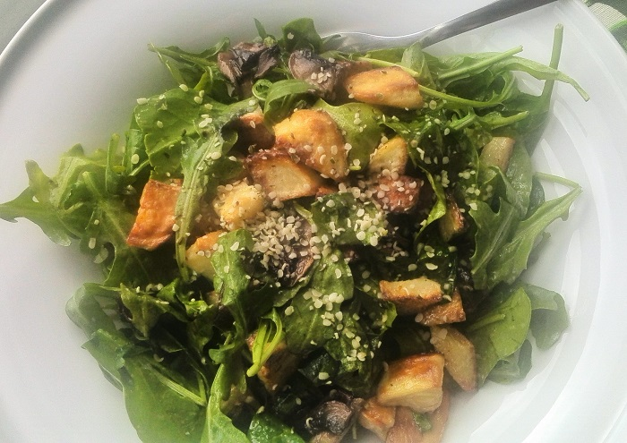 Roasted potato and mushroom salad on spinach and arugula with hemp seed